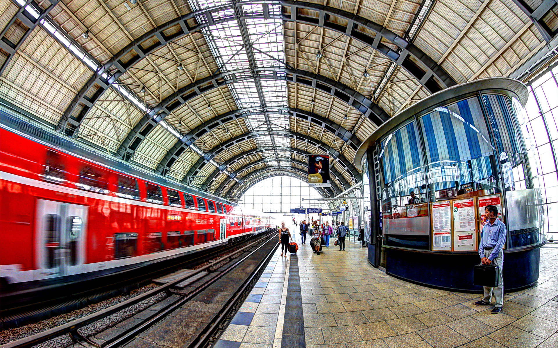 One of Deutsche Bahn's red regional double-deck trains dashing through a Berlin station (photo © Andrea Calistri).